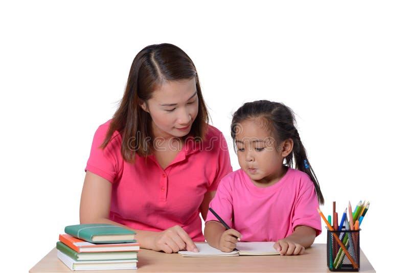 Jonge Leraar die kind met het schrijven van les helpen die op witte achtergrond wordt ge?soleerd royalty-vrije stock fotografie