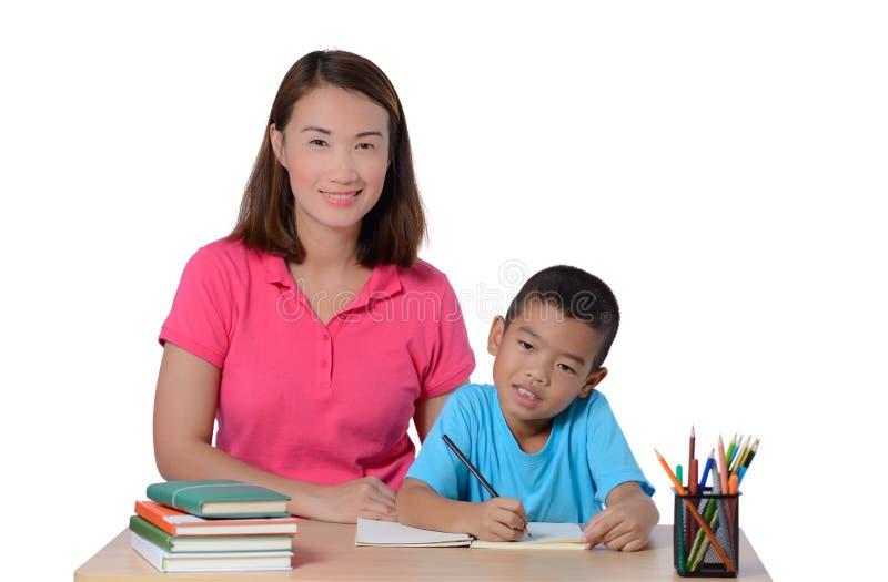 Jonge Leraar die kind met het schrijven van les helpen die op witte achtergrond wordt ge?soleerd royalty-vrije stock afbeeldingen