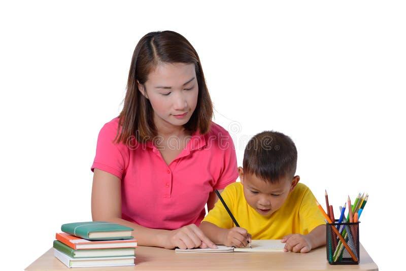 Jonge Leraar die kind met het schrijven van les helpen die op witte achtergrond wordt ge?soleerd stock fotografie