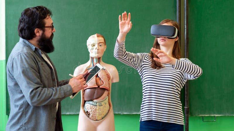 Jonge leraar die Virtuele Werkelijkheidsglazen en 3D presentatie gebruiken Onderwijs, VR, Tutoring, Nieuwe Technologieën en het O stock foto's