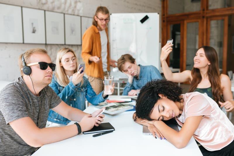 Jonge leraar die zich dichtbij raad bevinden en op studenten gillen terwijl zij ` t luisterend hem tijdens les aren Groep van stock afbeelding