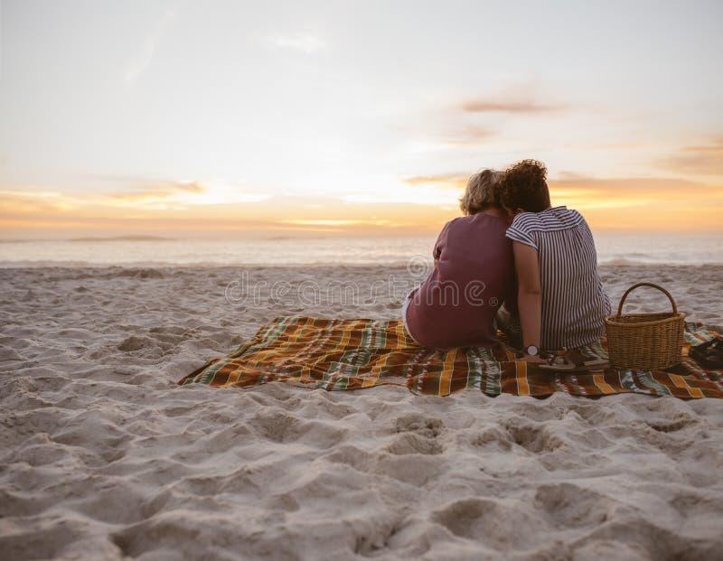 Jonge lesbische paarzitting op stranddeken die op de zonsondergang letten stock afbeelding