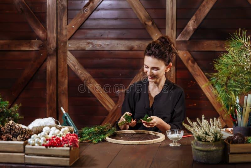 Jonge Leuke glimlachende Vrouwenontwerper die Kroon van de Kerstmis de Altijdgroene Boom voorbereiden Fabrikant van Kerstmisdecor stock afbeelding