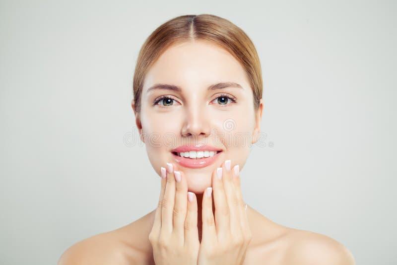 Jonge leuke vrouw die, close-upportret glimlachen Het mooie vrouwelijke gezicht met lippen met glanzende roze make-up en manicure stock foto's