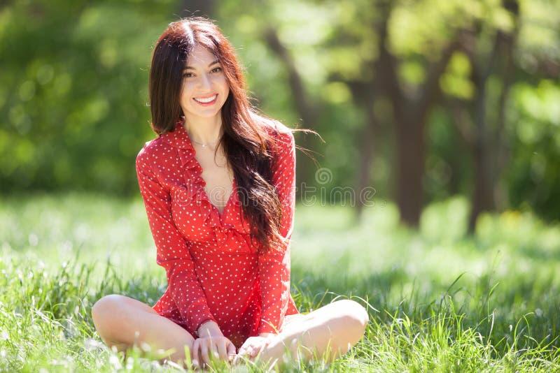 Jonge leuke vrouw in het rode kleding ontspannen in het park De sc?ne van de schoonheidsaard met kleurrijke achtergrond, bomen bi royalty-vrije stock afbeelding