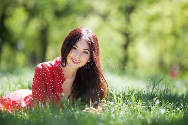 Jonge leuke vrouw in het rode kleding ontspannen in het park De sc?ne van de schoonheidsaard met kleurrijke achtergrond, bomen bi stock afbeelding