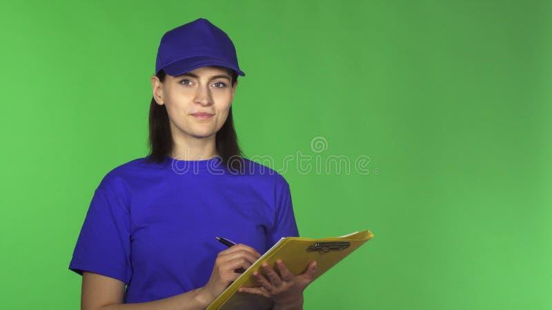 Jonge leveringsvrouw die documenten controleren op een klembord die aan de camera glimlachen stock afbeelding