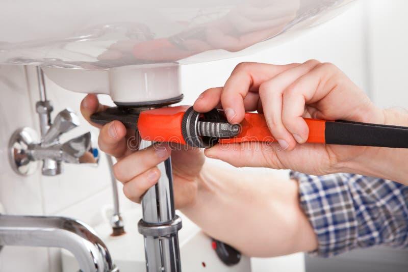 Jonge loodgieter die een gootsteen in badkamers bevestigen royalty-vrije stock afbeelding