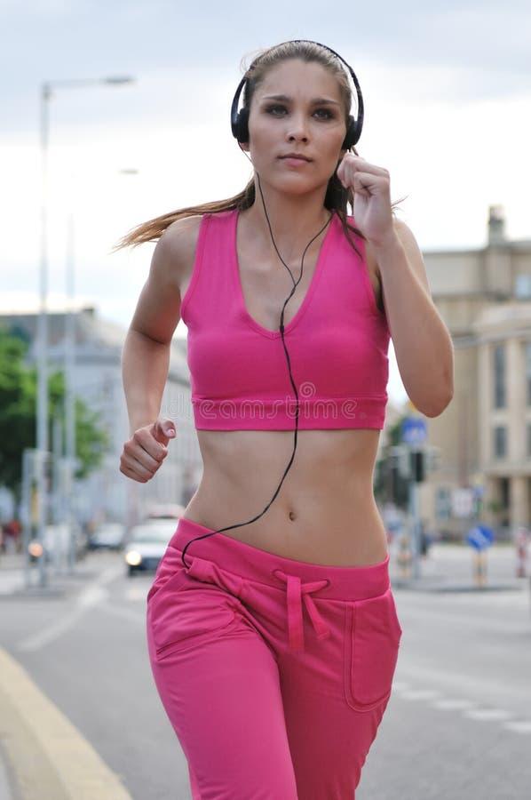 Jonge lopende vrouw het luisteren muziek royalty-vrije stock afbeeldingen