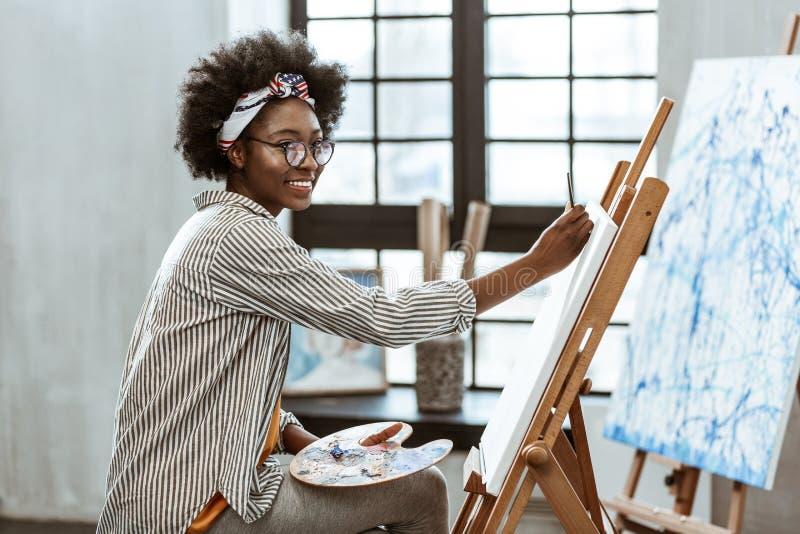 Jonge maar veelbelovende kunstenaar die terwijl de hele dag door het schilderen glimlachen royalty-vrije stock foto