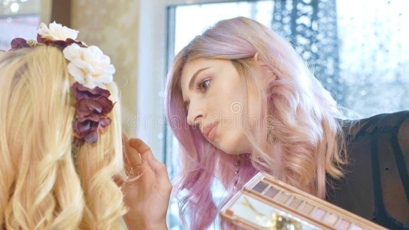Jonge make-upkunstenaar die schoonheidsmiddelen op de modelogen van ` toepassen s royalty-vrije stock foto's