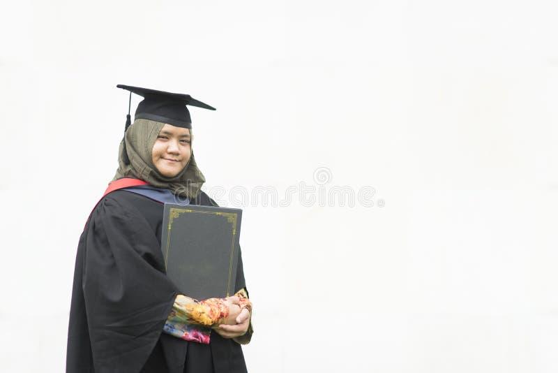 Jonge Maleise vrouw die een graadcertificaat houden terwijl het glimlachen op haar die graduatiedag op witte achtergrond wordt ge royalty-vrije stock fotografie