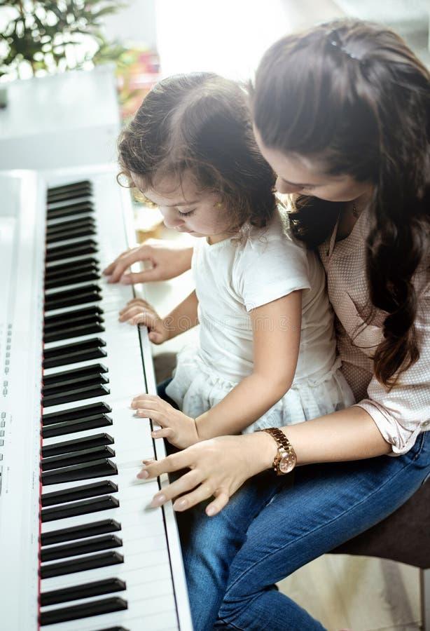Jonge mamma het spelen piano met haar weinig dochter stock fotografie