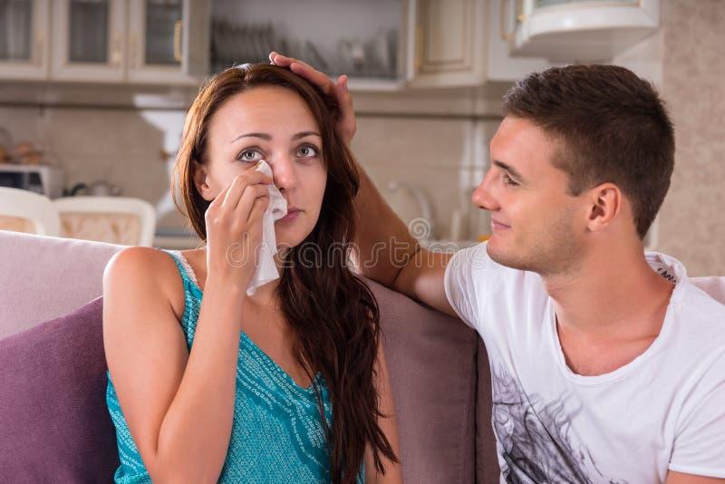 Jonge Man die Emotionele Vrouw thuis troosten royalty-vrije stock afbeelding