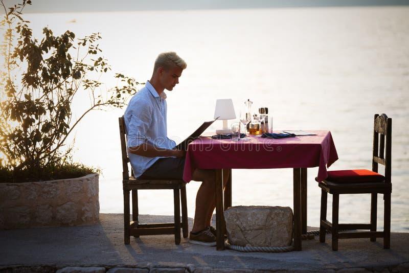 Jonge man die op vrouw in restaurant wachten royalty-vrije stock afbeeldingen