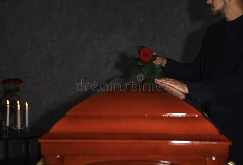 Jonge man die rode roos op deksel zet in begrafenis, staakt royalty-vrije stock fotografie