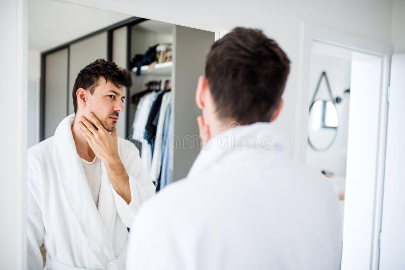 Jonge man die 's ochtends in een spiegel kijkt in de slaapkamer, dagelijkse routine stock fotografie