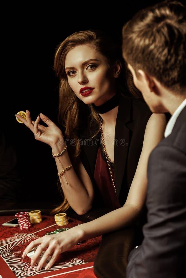 Jonge man die schitterende vrouw met pookspaander bekijken in casino stock foto's