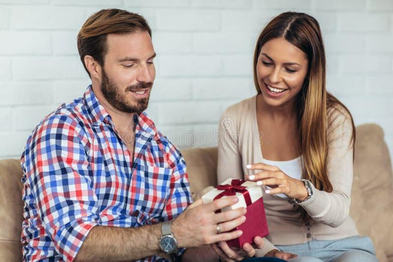 Jonge man die vrolijke vrouw met een giftdoos thuis verrassen stock fotografie
