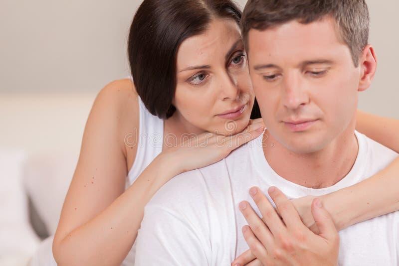 Jonge man en vrouw in bed het spreken royalty-vrije stock afbeelding