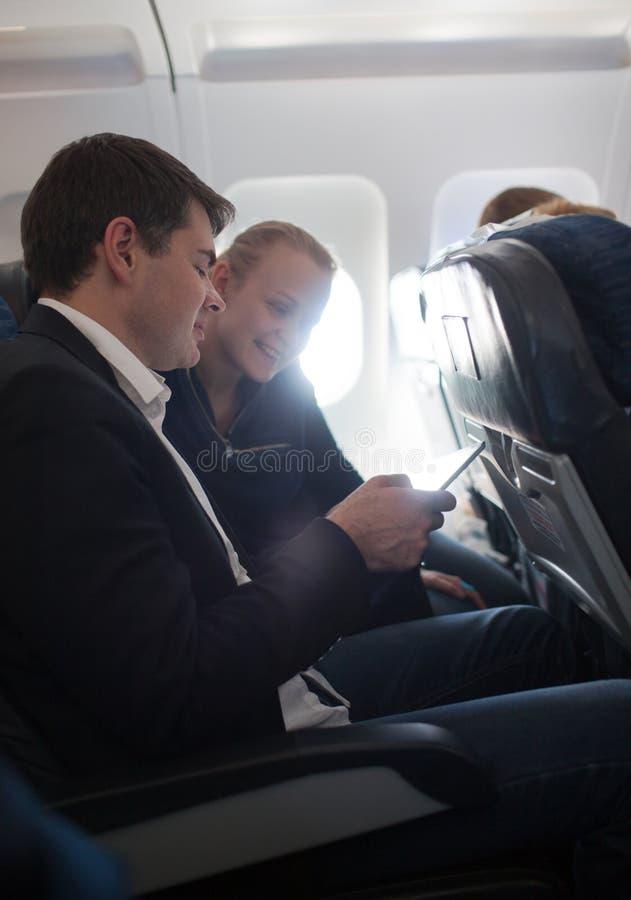Jonge man en vrouw die celtelefoon in vliegtuig met behulp van royalty-vrije stock foto