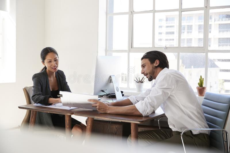Jonge man en vrouw die documenten over bureaus bekijken stock afbeelding