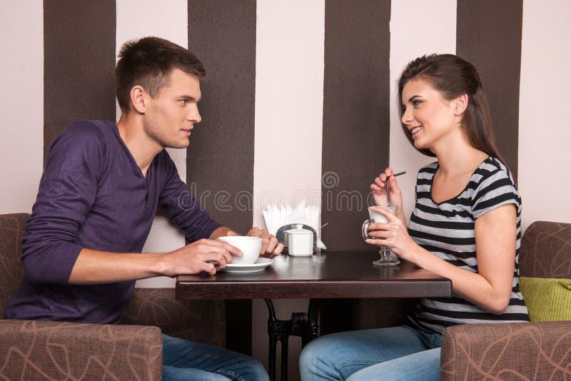 Jonge man en vrouw die in koffiewinkel spreken stock foto's