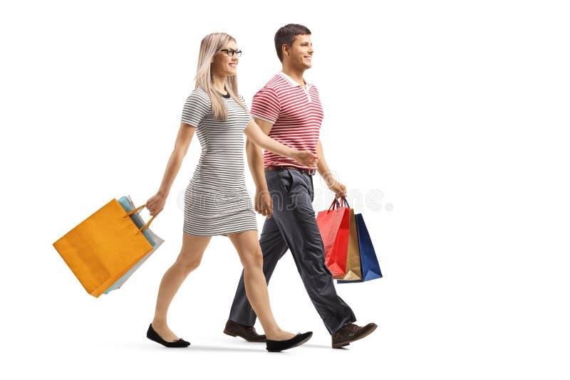 Jonge man en vrouw die met het winkelen zakken lopen stock foto