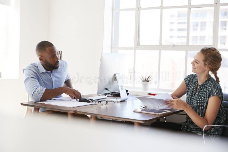 Jonge man en vrouw die over hun bureaus in een bureau spreken stock afbeeldingen