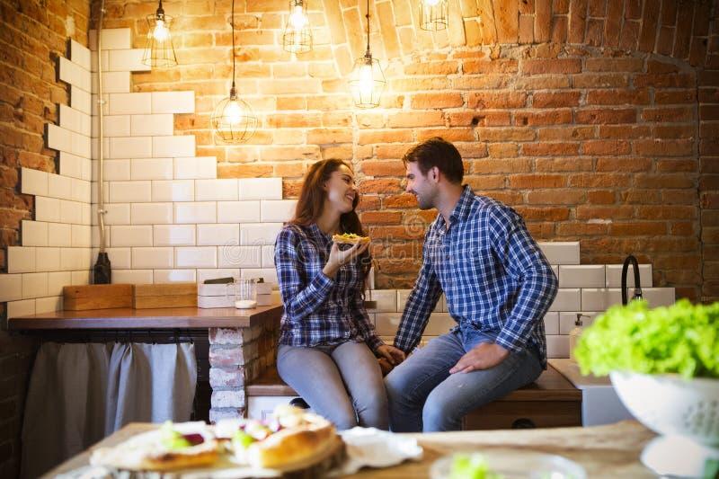 Jonge man en vrouw die en samen bij keuken koken eten stock fotografie