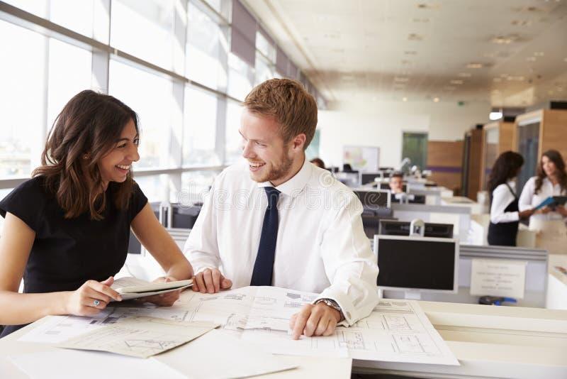 Jonge man en vrouw die samenwerken in architect? s bureau stock foto's