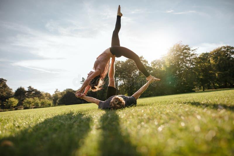 Jonge man en vrouw die yoga in paar doen stock foto's