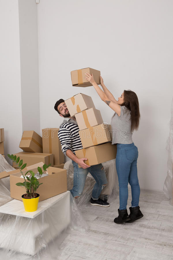 Jonge man en vrouw die zich in nieuw huis bewegen, die veel kartondozen houden royalty-vrije stock afbeeldingen
