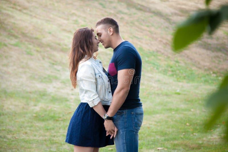 Jonge man en vrouw die zich in park nestelen stock afbeeldingen