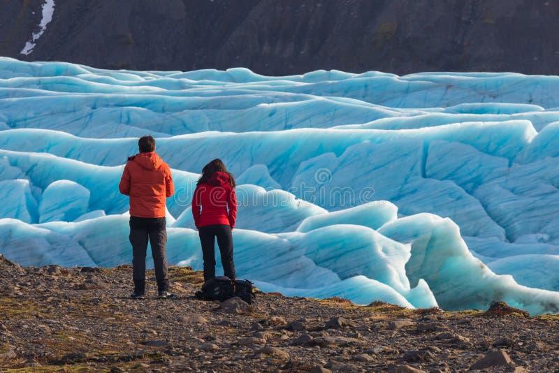 Jonge man en vrouw die zich voordien van mooi avondlandschap bevinden van Skaftafell-het Nationale Park van gletsjervatnajokull i royalty-vrije stock fotografie