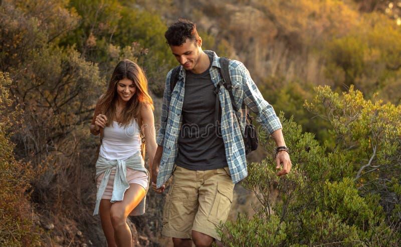 Jonge man en vrouw door bergsleep Gelukkig jong paar die samen wandelen royalty-vrije stock foto's