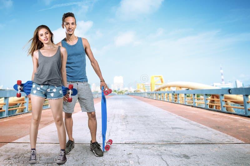Jonge man en vrouw met skateboard stock foto