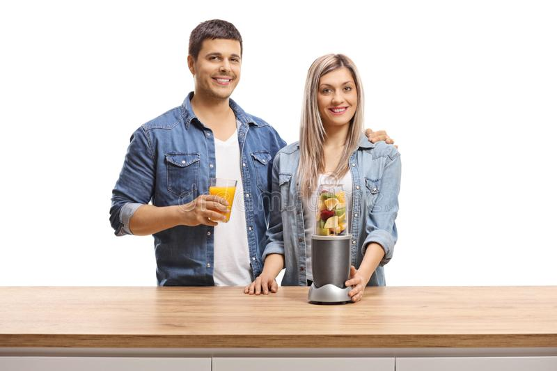 Jonge man en vrouw met vruchten in een mixer en een glas sap die bij de camera glimlachen royalty-vrije stock fotografie