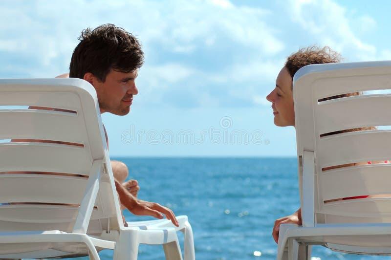 Jonge man en vrouw op strand stock afbeelding
