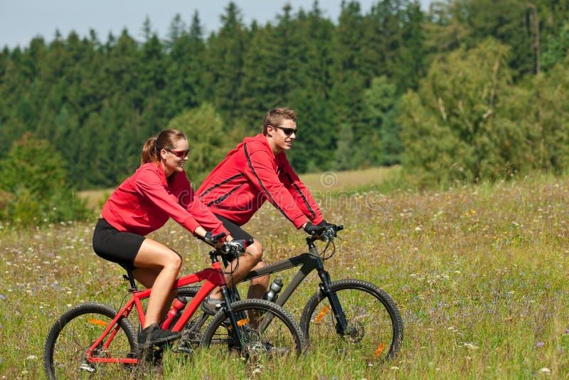 Jonge man en vrouwen berijdende bergfiets stock foto