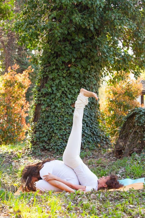 Jonge man en vrouwen de yoga van de praktijkpartner openlucht in houten de zomerdag royalty-vrije stock foto's
