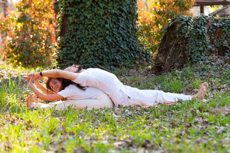 Jonge man en vrouwen de yoga van de praktijkpartner openlucht in houten de zomerdag royalty-vrije stock fotografie