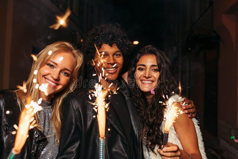 Jonge man en vrouwen die van nieuwe jarenvooravond genieten stock afbeelding