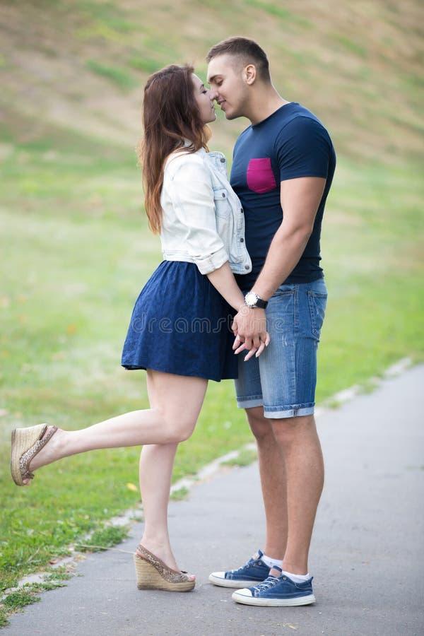 Jonge man en vrouwen het kussen in park stock foto