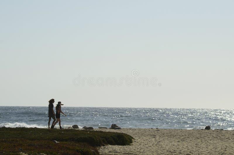Jonge man en vrouwen het paar silhouetteert het lopen Vreedzaam strand Baja, Mexico stock fotografie