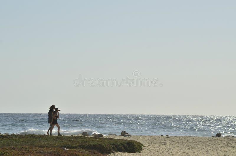 Jonge man en vrouwen het paar silhouetteert het lopen Vreedzaam strand Baja, Mexico stock foto's