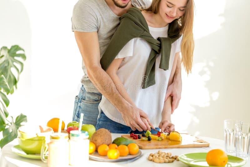 Jonge man en vrouwen wcutting ingrediënten zeer zorgvuldig royalty-vrije stock foto's