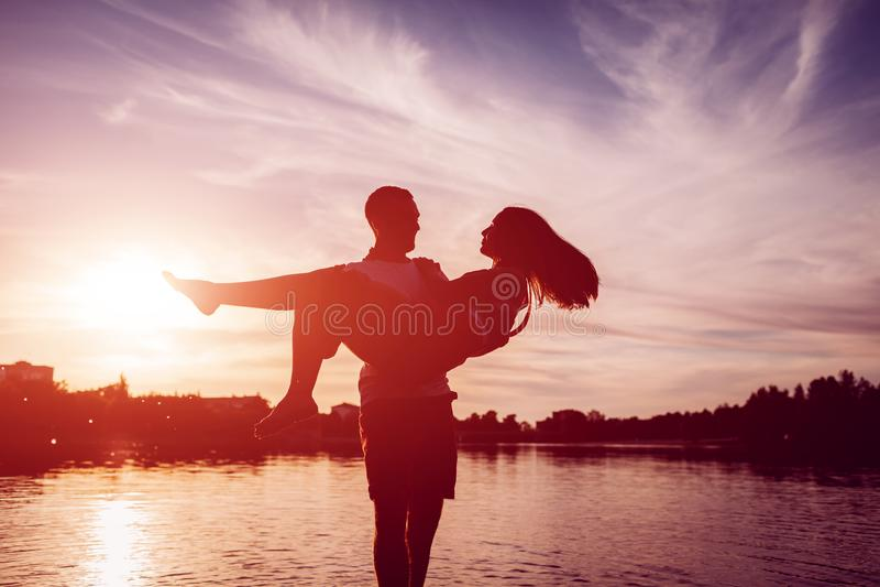 Jonge man holdingsvrouw op de bank van de de zomerrivier Paar die pret hebben bij zonsondergang Kerels het koelen royalty-vrije stock foto's