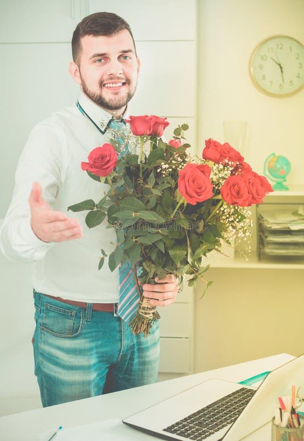 Jonge man klaar om bloemen aan vrouw voor te stellen royalty-vrije stock afbeeldingen