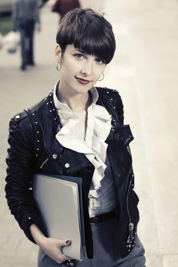 Jonge manier bedrijfsvrouw die in leerjasje met omslagen in stadsstraat lopen royalty-vrije stock foto